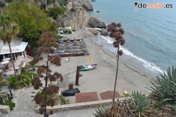 The small beach is dark sand and has beach bars, sunbeds and showers.